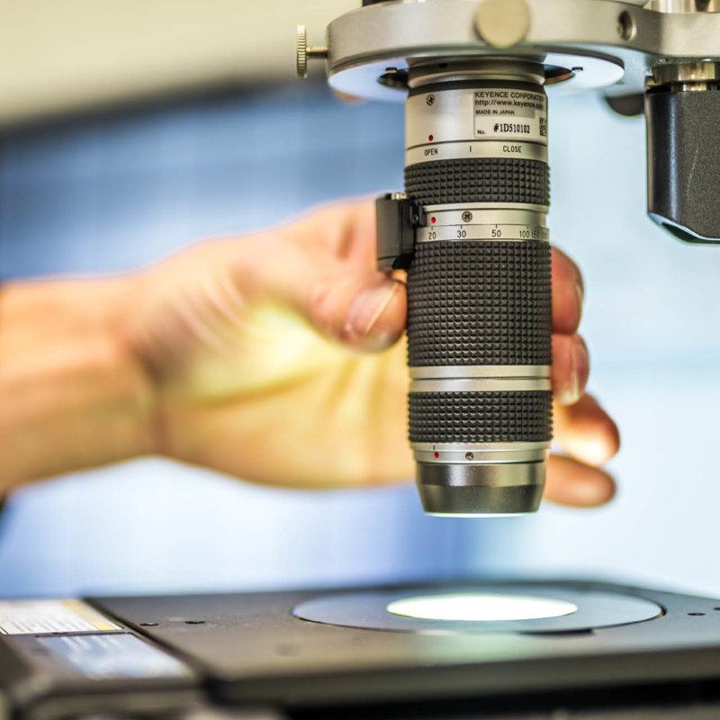 Employee operates microscope
