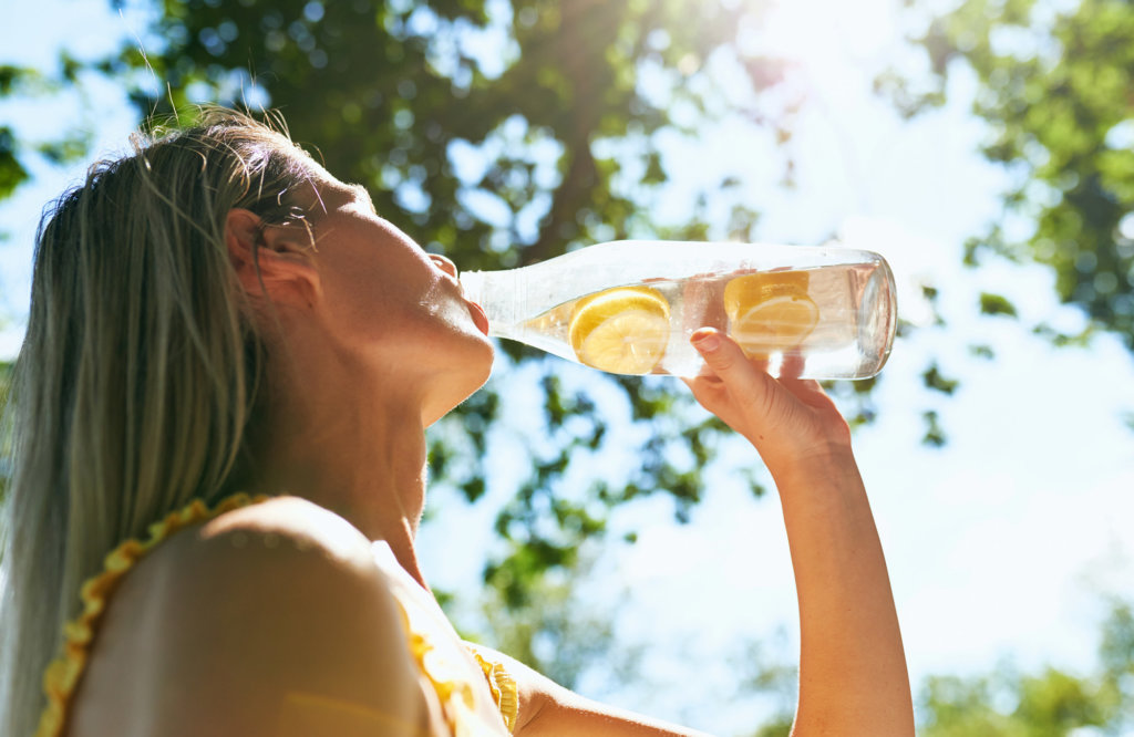 Woman drinking from a glass bottle with fruits