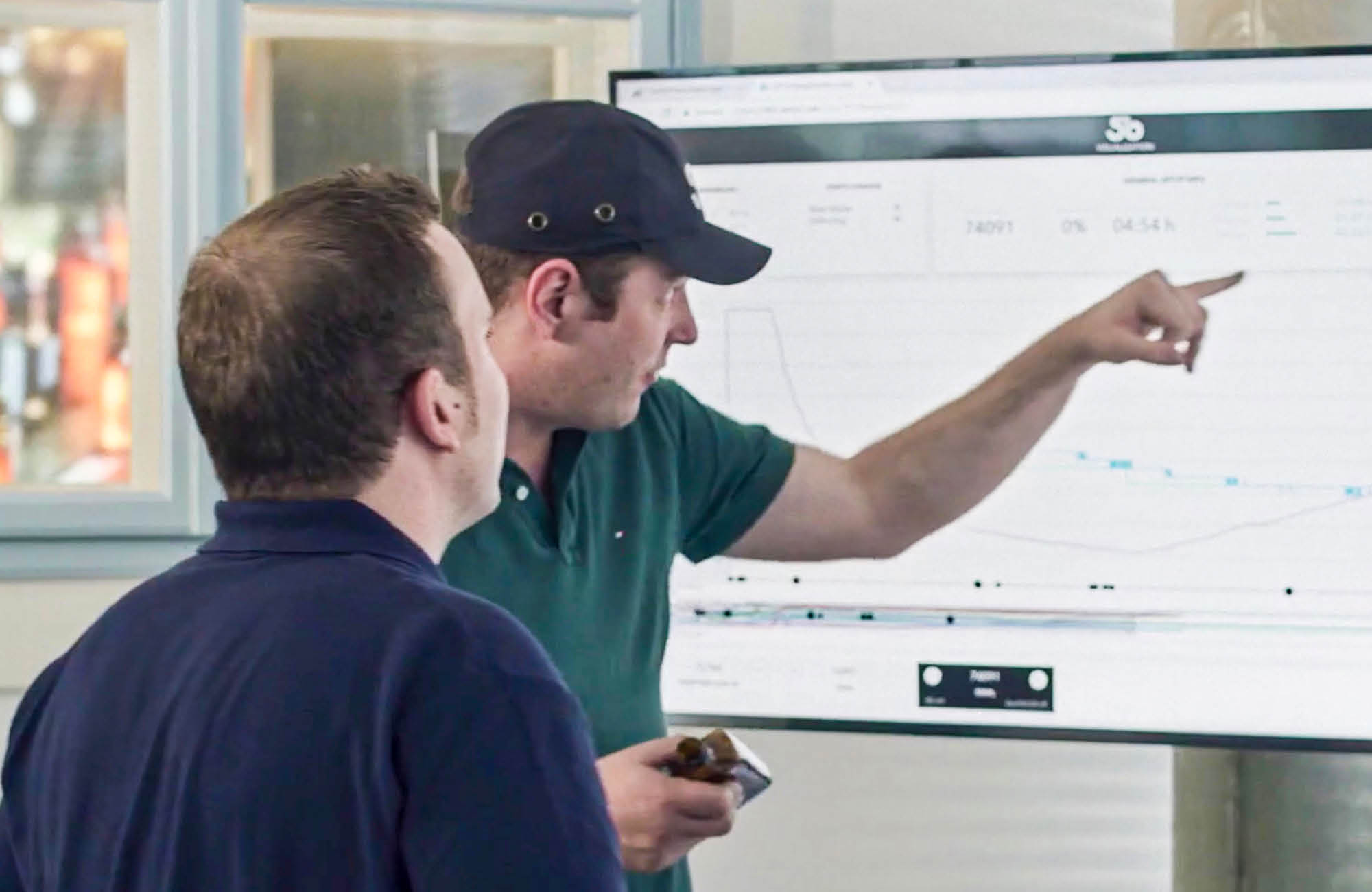 Two persons are discussing the production process in front of a screen