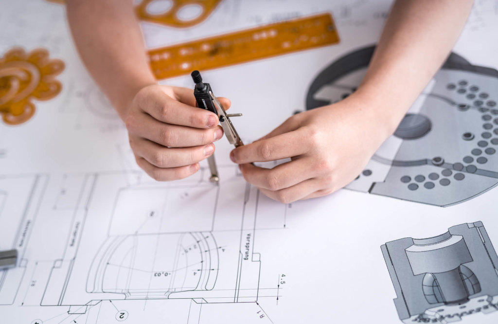 Technical drawing and hands of a person doing modifications