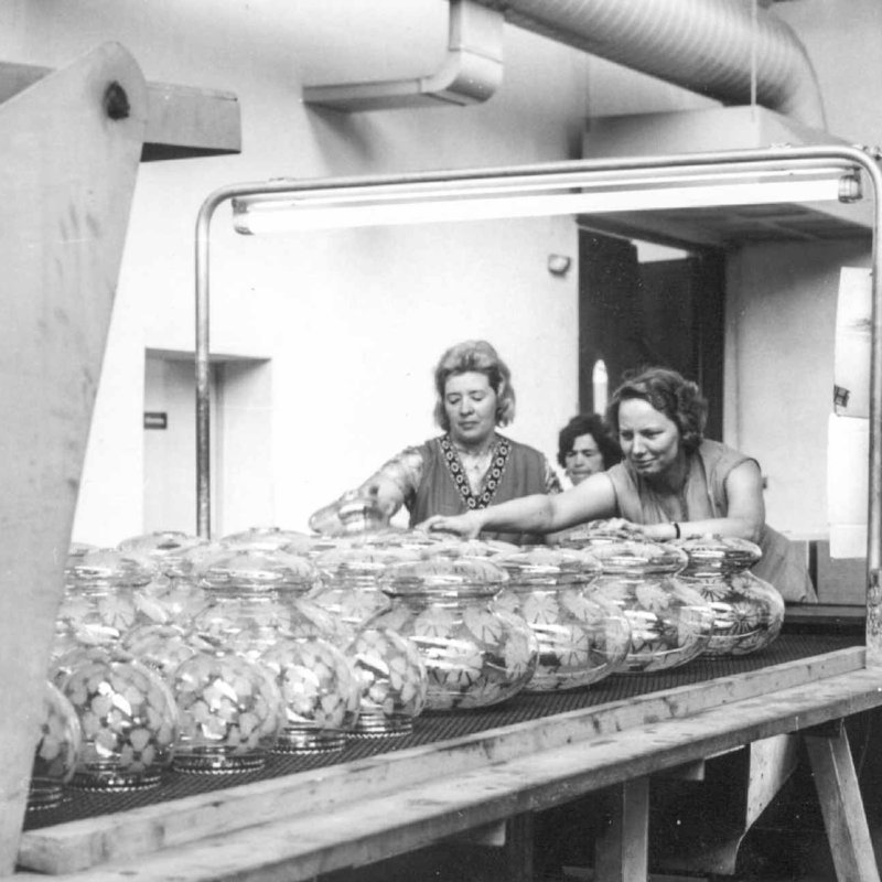 Historic picture showing women sorting and packing mouthblown glassware